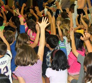 Students raising their hands at the all school assembly